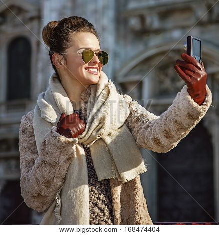 Traveller Woman In Milan With Digital Camera Taking Selfie