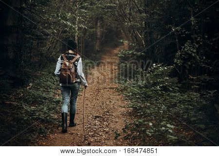 Hipster Traveler With Backpack Walking In Woods. Stylish Woman Hiking. Wanderlust And Travel Concept