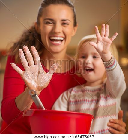 Closeup on mother and baby hands smeared in flour