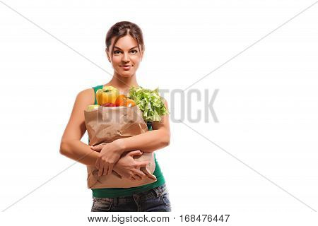 Portrait of beautiful smiling woman holding shopping paper bag with organic fresh food isolated on white background. concept of healthy food nutrition
