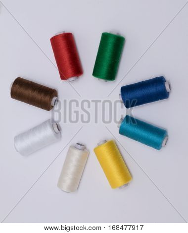 several bobbin of colourfull threads in circle