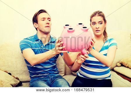 Couple with piggy bank sitting on sofa