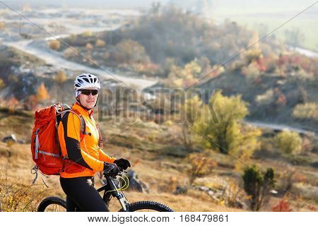 cyclist-traveler with a backpack on mountain bike rides on a mountain trail in spring season. countryside. beautiful landscape. cyclist in white helmet with red backpack.
