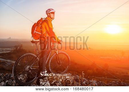 cyclist on mountain-bike at sunset, cyclist on the background of beautiful sunset. cyclist with white helmet and red backpack. beautiful landscape. back view.