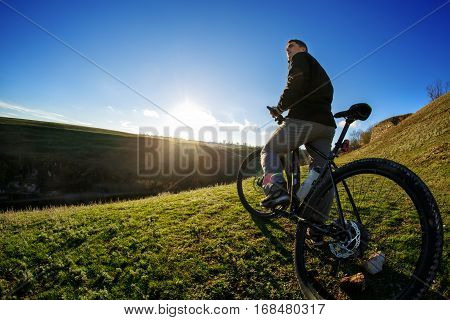 low angle view of cyclist standing with mountain bike at sunrise against bright sun and blue sky. sping season. Horisontal wide angle fisheye photo