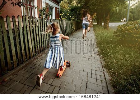 Happy Cute Girl In Stylish Dress Riding Scooter In Sunny Street, Amazing Family Moment