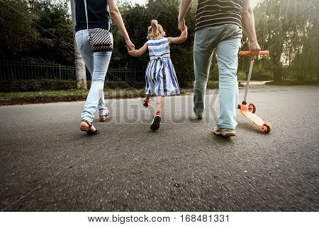Happy Stylish Parents Holding Hands With Daughter And Walking In Sunny  Street, Amazing Family Momen