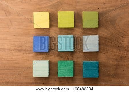 Index, menu or cover abstract back ground, consisting of nine hand painted colored wooden cubes on grungy wooden background with vintage taste.  Green, bluye, yellow.