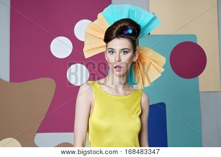 Danish design. Eccentric outfit: yellow dress with open shoulders, headdress made of paper, mouth open. Color background: circles, rectangles