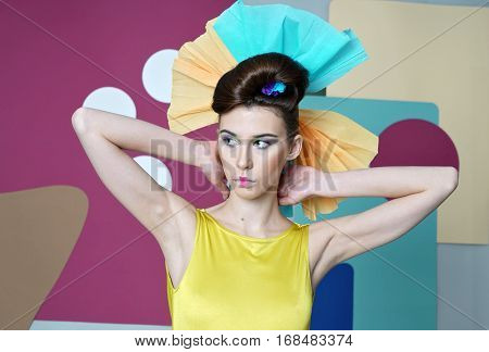 Eccentric outfit: short dress with open shoulders, headdress made of paper, hand behind head. Multicolor background: circles, rectangles