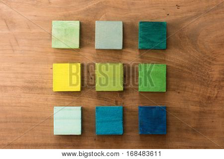 Index, menu or cover abstract back ground, consisting of nine hand painted colored wooden cubes on grungy wooden background with vintage taste.  Green, yellow-green, blue, mint.