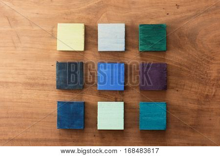 Index, menu or cover abstract back ground, consisting of nine hand painted colored wooden cubes on grungy wooden background with vintage taste.  Green, blue, violet.