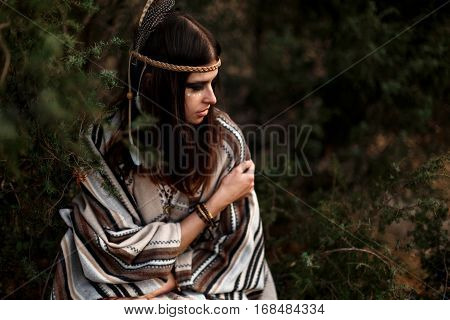 Beautiful Native Indian American Woman With Warrior Shaman Make Up Sitting On Background Of Woods