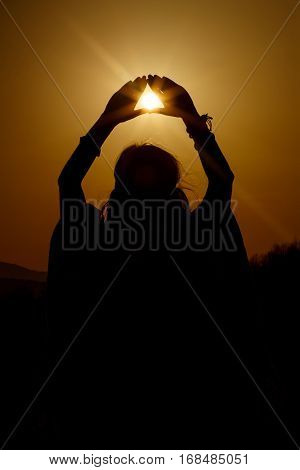 Silhouette Of Woman Hands Holding Sun In Triangle On Background Of Beautiful Sunset