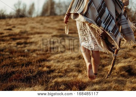 Woman Legs In Native Indian American Boho Dress Walking In Windy Sunny Evening Mountains, Holding Fe