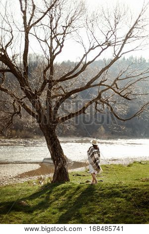 Beautiful Woman Hipster Wearing Hat And Poncho Walking At Tree Near River, American Outfit, Boho Con