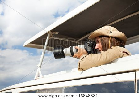 Young woman on African safari standing in open roof jeep and taking pictures with professional camera
