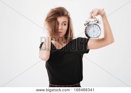 Portrait of a young upset woman with messy hair holding alarm clock over white background