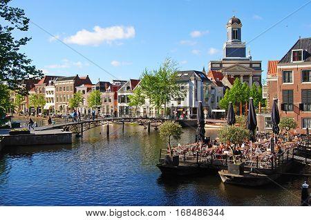Leiden, The Netherlands - May 13, 2014. View over Nieuwe Rijn river in Leiden, with cafe, Waaghoofdbrug bridge, historic buildings, people and Hartebrugkerk in the background.