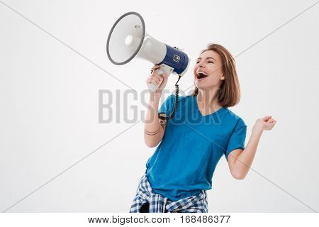Portrait of a casual excited woman screaming in loudspeaker isolated on a white background