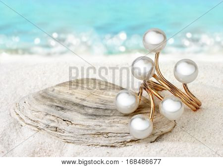 Jewellery ring with pearls on sand beach background soft focus