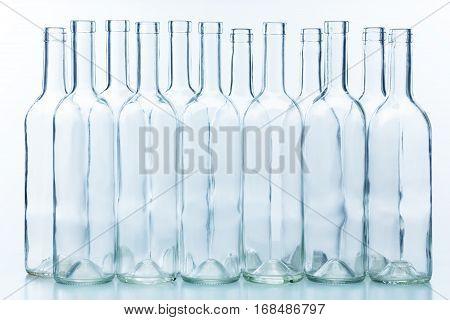 A dozen empty wine bottles arranged chess-board fashion isolated on white