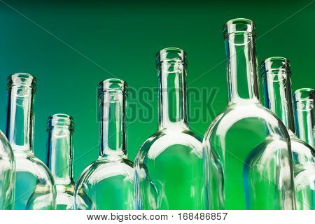 Picture of seven empty wine bottles' bottlenecks against a green background