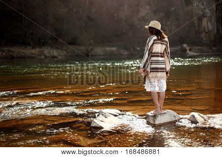 Beautiful Woman Traveler Back Standing On Rocks In River, Wearing Hat And Poncho, Boho Travel Concep