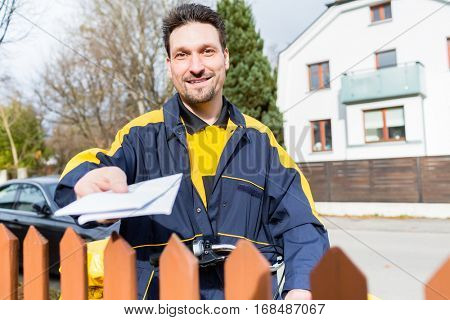 Mailman passing letters to addressee over fence