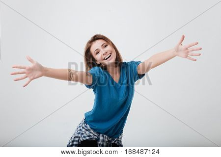 Portrait of a happy young girl with outstretched hands to embrace you isolated on a white background