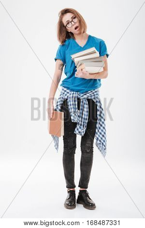 Full length portrait of a tired exhausted student standing and holding heavy books isolated on the white background