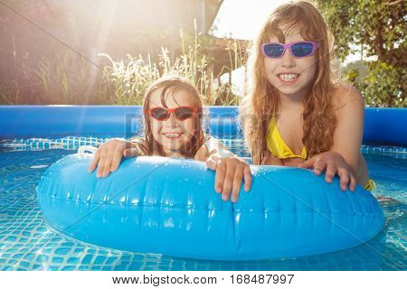 Portrait of two blond girls in sunglasses swimming in the inflatable pool with blue rubber ring
