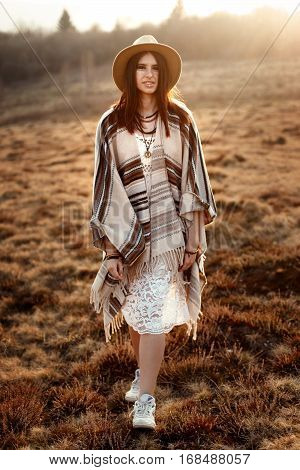 beautiful woman hipster posing wearing hat and poncho at sunset in mountains