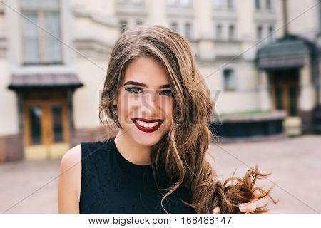 Closeup portrait of effective girl with long curly hair smiling to camera on street on building background. She wears black dress, vinous  lips.
