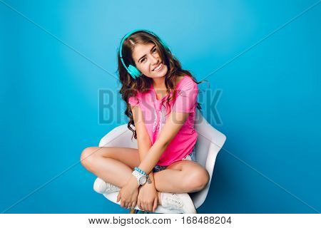 Cute  girl with long curly hair chilling in chair on blue background. She wears shorts, pink T-shirt, white sneakers. She is listening to music, keeps legs crossed on chair.