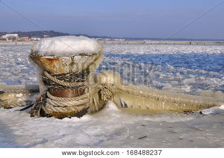 Ships mooring bollard on the background of frozen river