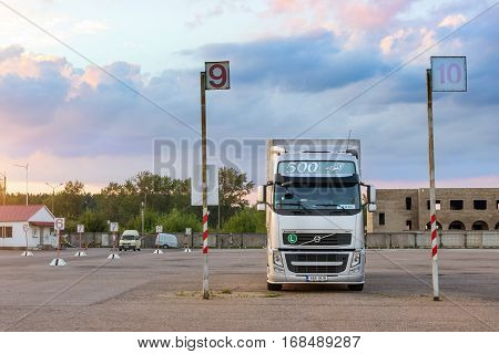 Narva Estonia - August 20 2016: Volvo heavy truck loaded with goods trailer parked in waiting area on Estonian-Russian state border crossing. International hard transportation and logistics. Transport infrastructure