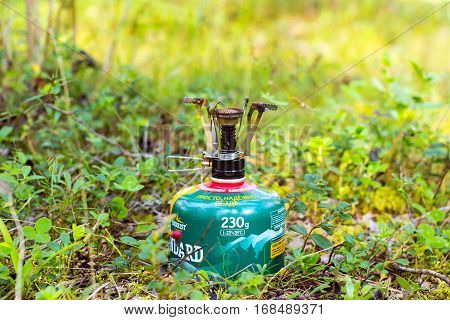 Alutaguse Seikluspark Estonia - August 28 2016: Touristic camping burner installed on gas cylinder tank in background of summer forest. Compact kitchen stove for cooking hot food in field travel conditions. Alutaguse Adventure Park