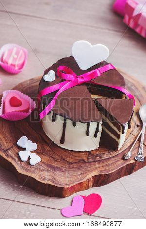 Chocolate cake with romantic white and pink heart shaped decoration and petit fours