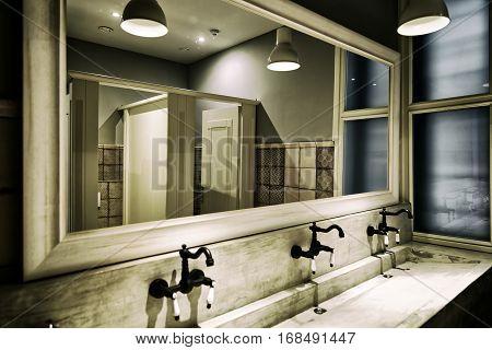 modern public toilet with washbasin under lights