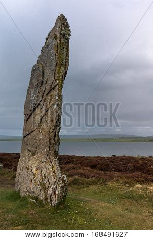 Orkneys Scotland - June 5 2012: Ring of Brodgar Neolithic Stone Circle. Closeup of menhir with white and yellow mold spots stands erect on a grass field under gray cloudy sky. Hills and Loch of Harray in the background.