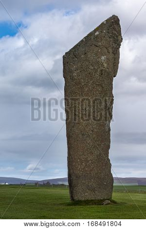 Orkneys Scotland - June 5 2012: Ring of Brodgar Neolithic Stone Circle. Closeup of menhir with white and yellow mold spots stands erect on a grass field under blue cloudy sky. Hills and farm in the background.