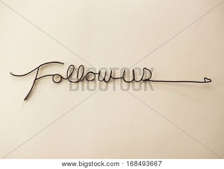 Follow us sign made from black steel wire, placed on vintage tone paper.
