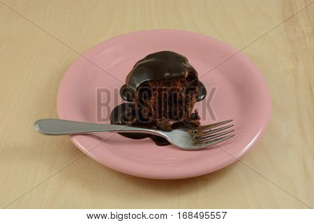 Partially eaten chocolate cupcake with chocolate chips and chocolate syrup topping on piate with fork