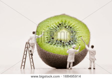 Miniature Painters coloring green kiwi. Macro photo.