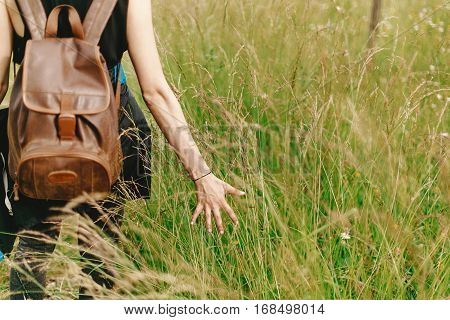 Stylish Hipster Traveler Walking In Grass And Holding  In Hand Herb  Wildflowers In Summer Mountains