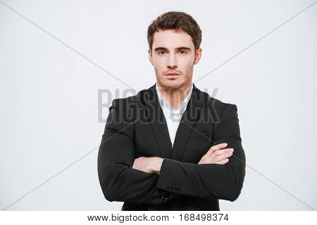 Portrait of a confident young business man in suit standing with arms folded isolated on a white background