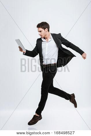 Full length portrait of a concentrated young business man jumping and looking at tablet computer isolated on a white background