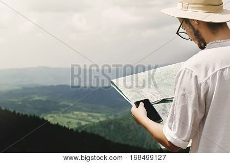 Stylish Hipster Traveler Holding Map And Phone With Empty Screen At Top Of Mountains With Amazing Vi