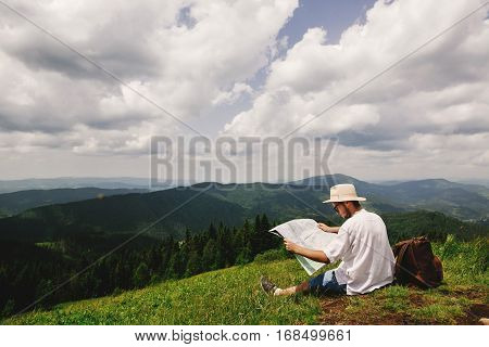 Stylish Hipster Traveler Man With Backpack Sitting At Top Of Mountains With Amazing View And Holding